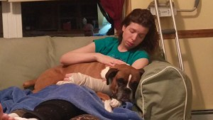 Dash the Boxer lays on Julia's lap while she's recovering from a broken leg and pinky.